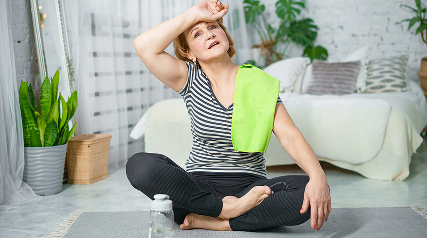 Woman sitting on yoga mat with arm wiping away sweat from brow