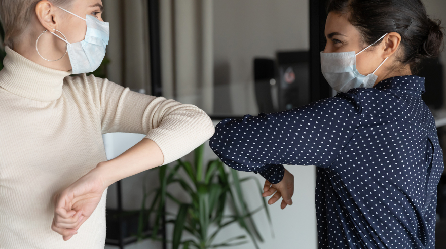 Two people in health masks doing an elbow bump