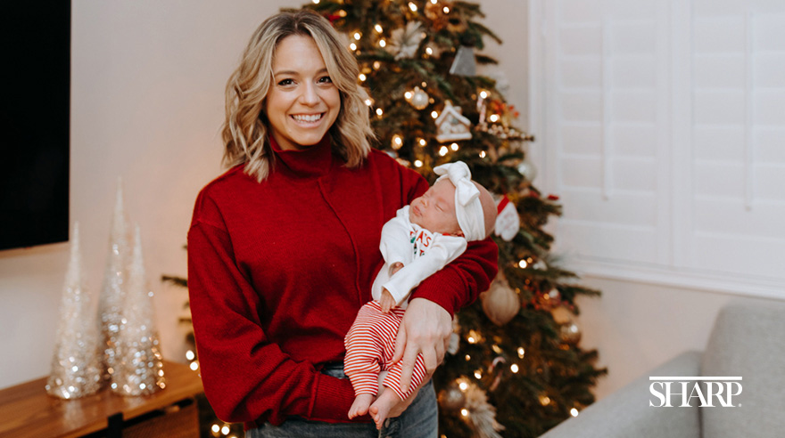 Woman holding infant in front of Christmas tree