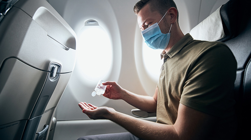 Man in mask on airplane using hand sanitizer