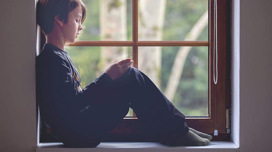 Sad boy sitting in window, One mom's quest for quality care for her son