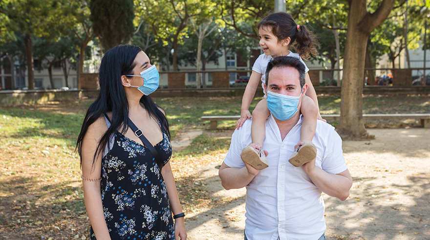 Father holds his 2-year-old girl in a park while her mother watches them while wearing protective masks.