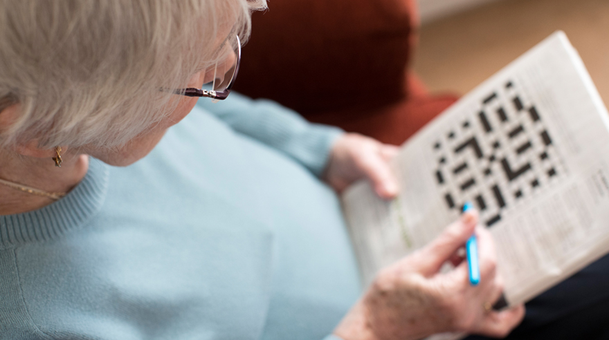 Older woman with crossword puzzle