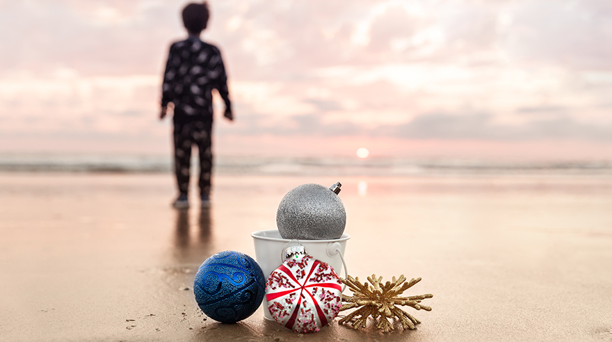 Ornaments on beach with child in pajamas in background