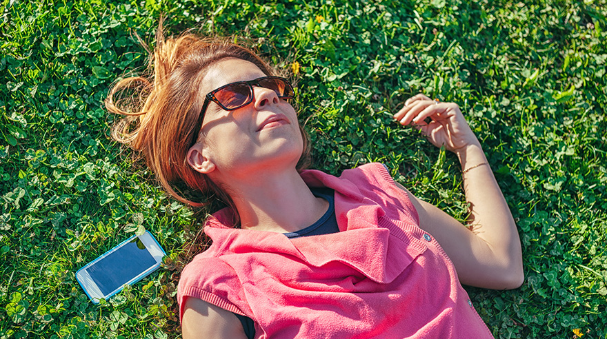 Woman with sunglasses lying in grass