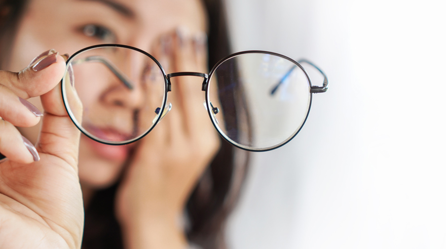 Woman with glasses experiencing eye pain and headache