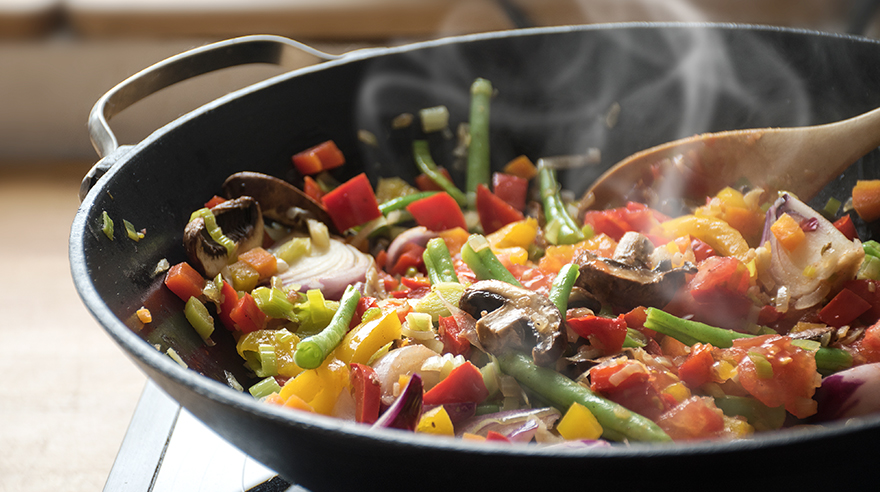 Vegetables cooking in a wok on the stove