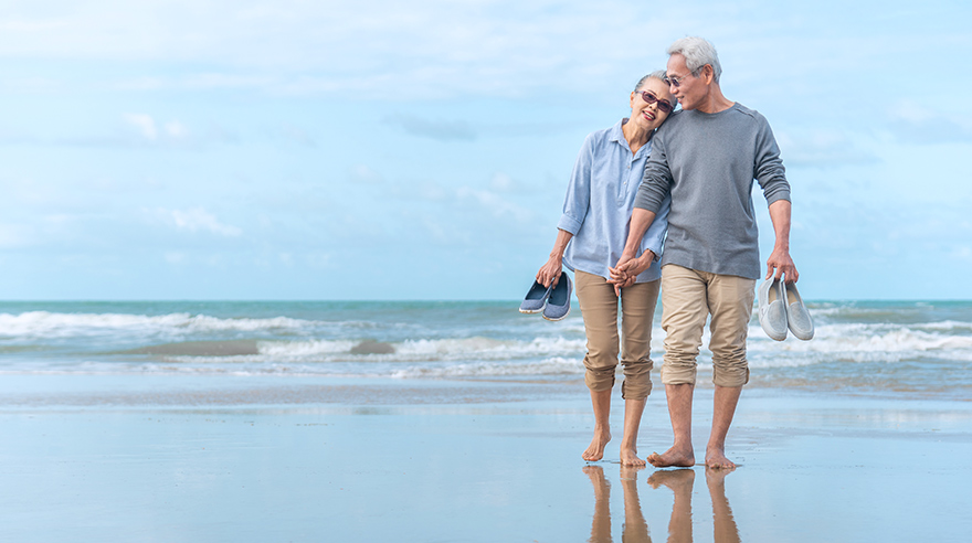 Older couple walking on beach