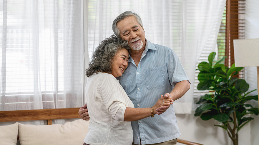 Grandparents dancing and hugging together with happy feeling in house