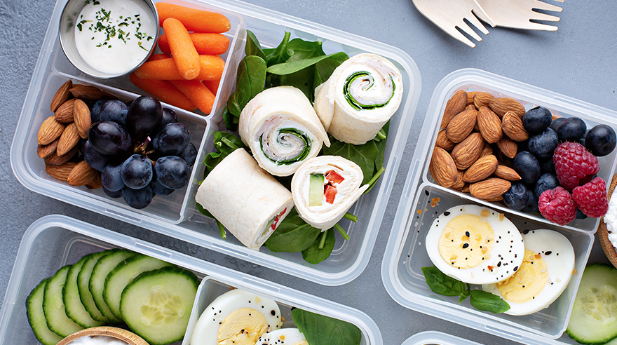 Meal prep lunch with eggs, nuts, carrots, berries and pinwheel sandwiches