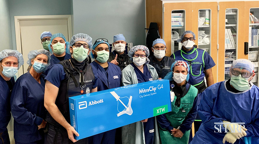 Dr. Jad Omran (left, in black vest), the Sharp Grossmont Hospital cardiac catherization lab team and representatives of Abbott pose with the MitraClip device, a minimally invasive treatment option for patients with mitral valve regurgitation.