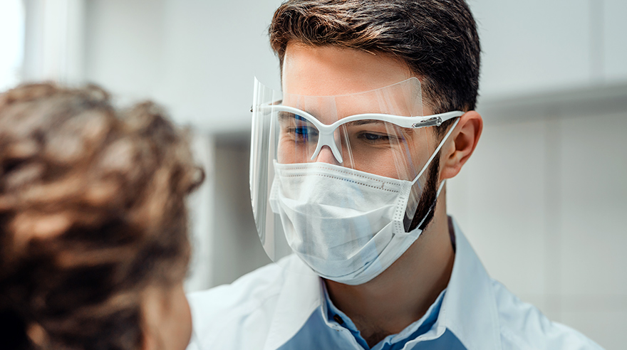 Doctor in mask and face shield talking to patient