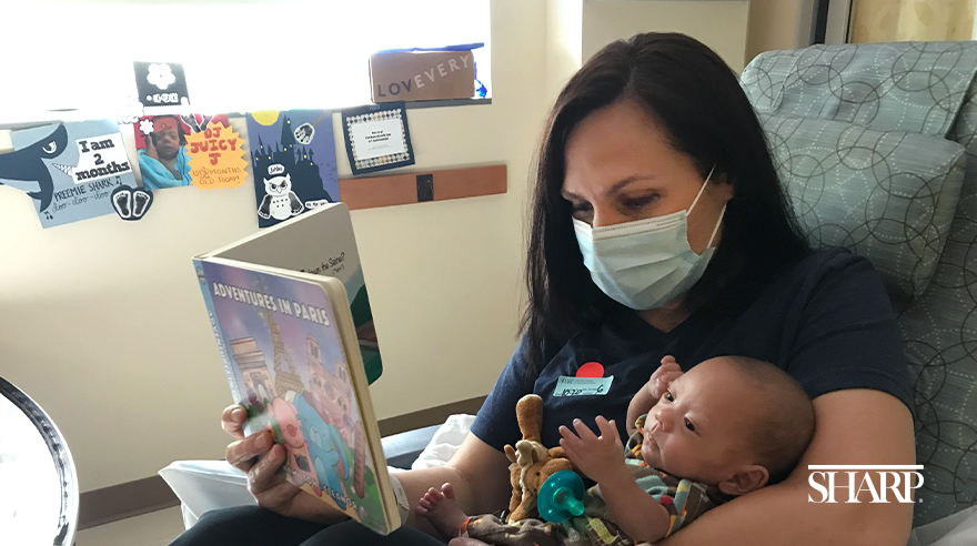 Melissa Stevenson reading a story to baby Jordan in the NICU at Sharp Mary Birch Hospital for Women & Newborns