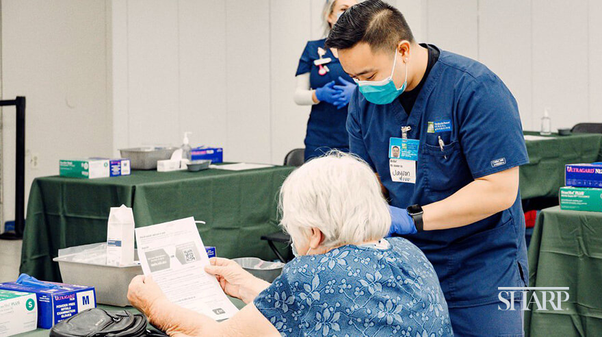 Volunteer assists patient at the Sharp COVID-19 vaccination clinic located in the former Sears building at Chula Vista Center.