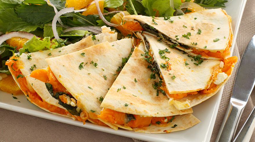 Pieces of pumpkin quesadilla on plate with a salad
