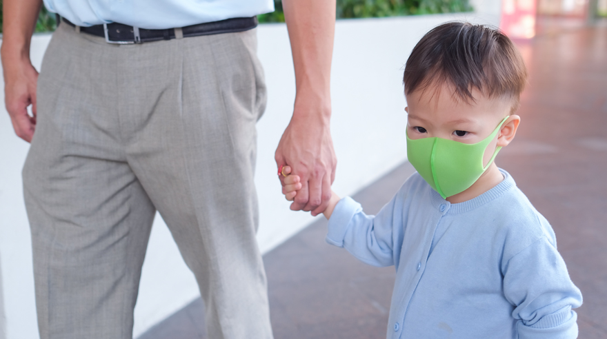 Young child walking with father, wearing a mask