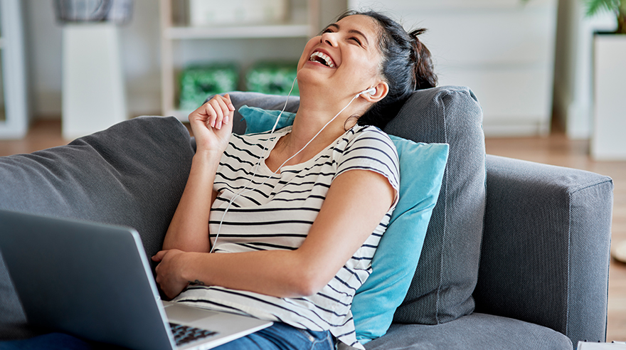 Woman laughing during a video conversation laying on couch