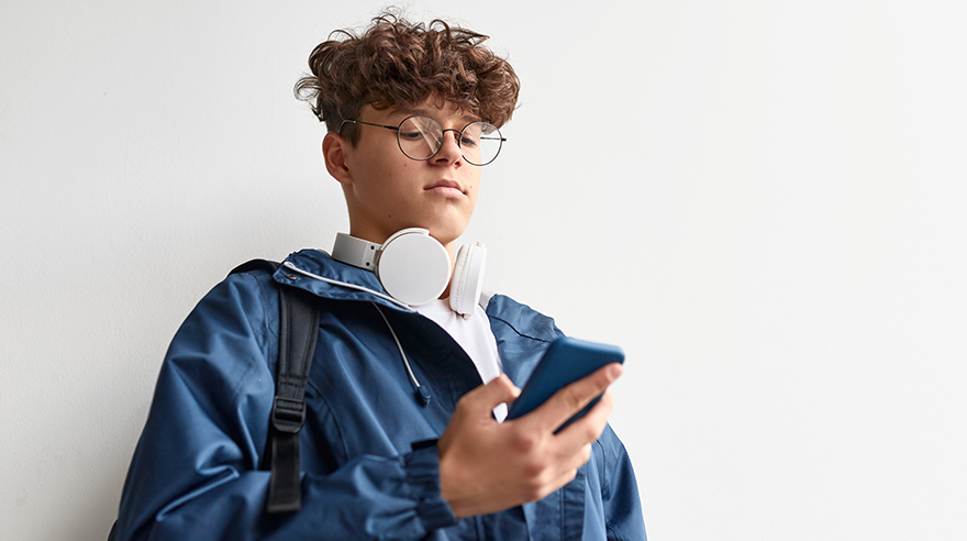 Young man on smart phone listening to headphones