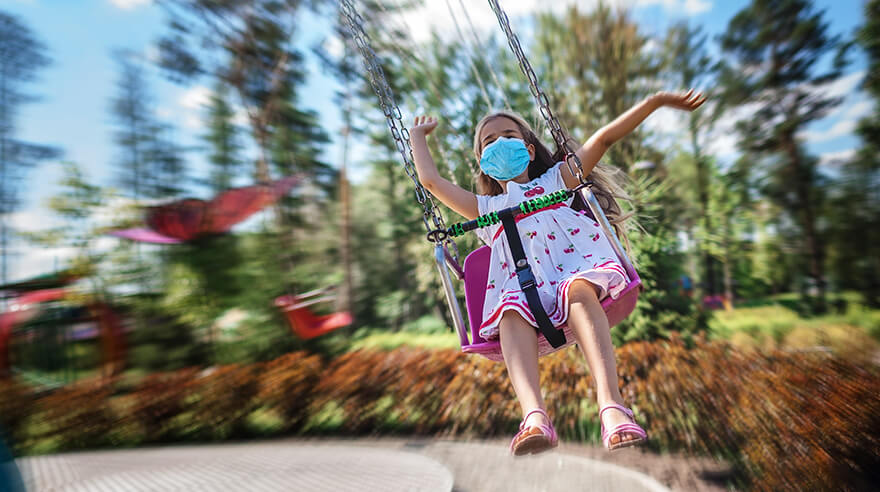 Girl wearing facial mask having fun at an amusement park.