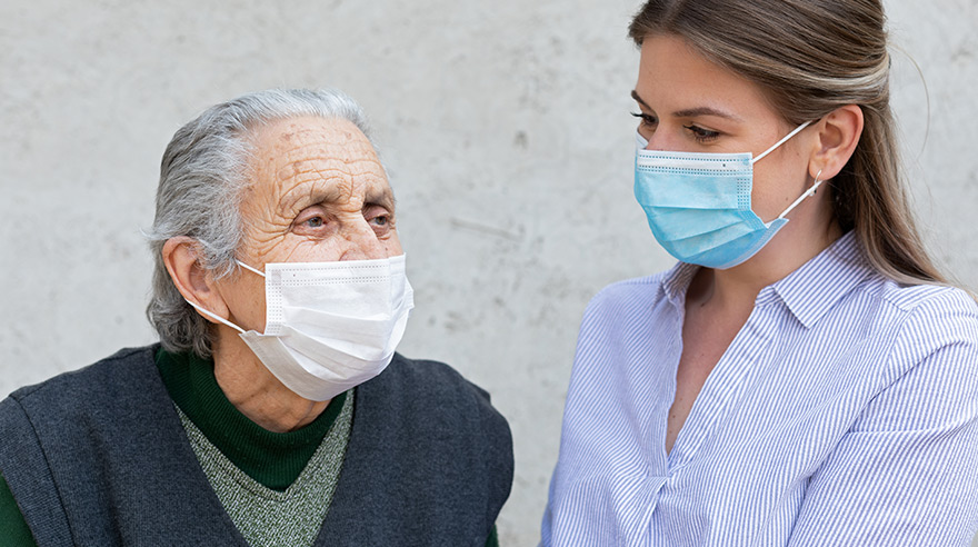 Caregiver works with elderly ill woman wearing mask because of COVID-19