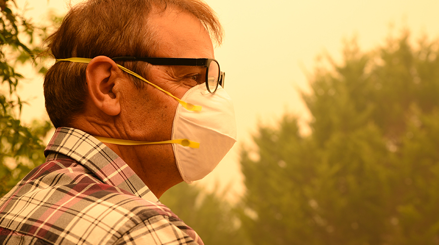 Man wearing glasses and mask in smoky air