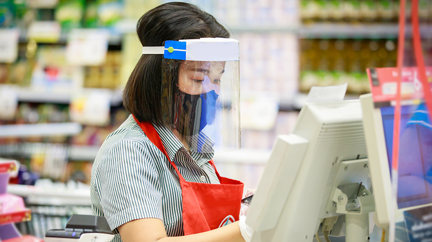 Retail worker wearing a face mask and face shield