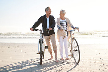 Man and woman riding bikes on beach